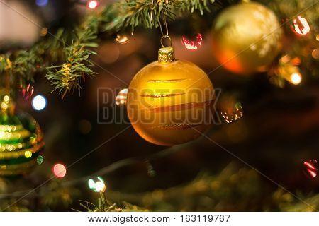 Christmas toys on the Christmas tree. Ball and festive lights. Close-up.