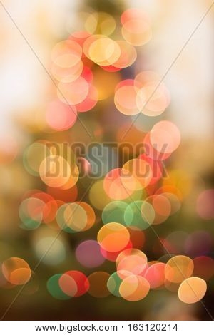 Blurred Background of the Christmas tree. Beautiful lights and bokeh. Warm colors and shades.