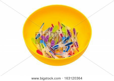 Multicolored, motley clothespins in a yellow bowl.