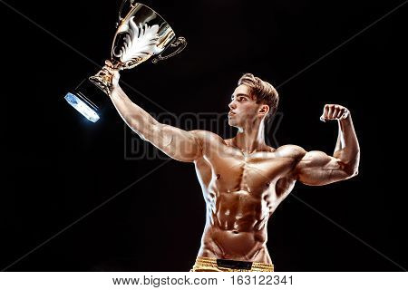 Portrait of shirtless muscular male with champion winning cup isolated on black background.