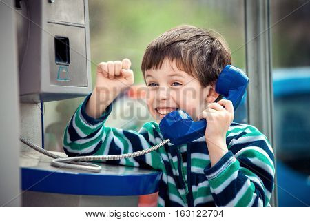 Cute little boy is calling home using the public payphone