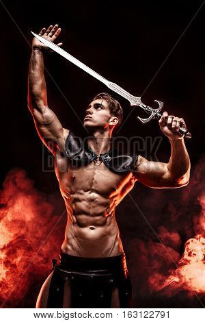 Young muscular model posing with sword in hands and looking away in fire background.