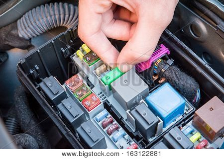Hand checking a fuse in the fuse box of a modern car engine