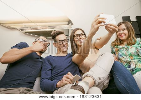 group of friends on couch takes a selfie