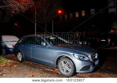 STRASBOURG FRANCE - DEC 06 2016: German Mercedes-Benz E Class car parked for night in front of luxury French house with Christmas tree in the yard