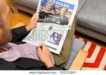 PARIS FRANCE - NOV 12 2016: Curious man reading Le Figaro French newspaper with Hillary Clinton and Donald Trump after Trump has won the elections