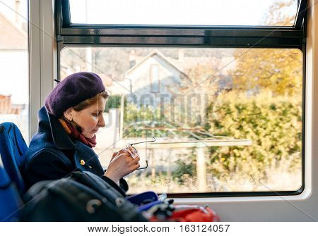 Smiling woman cleaning eyeglasses while driving in tramway with beautiful French village city seenthrough the window