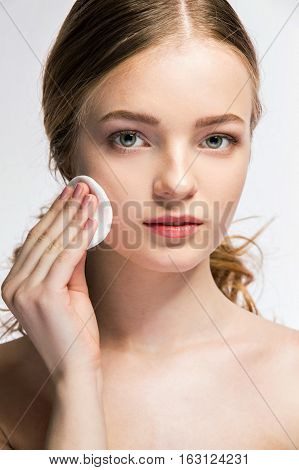 beauty concept of young woman with sponge and clean perfect skin looking at camera