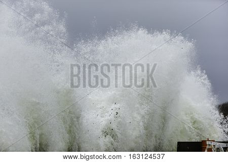 Wave erupts into air as it smashes into sea wall