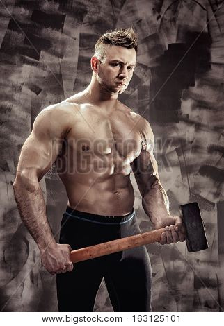 athlete and hammer - a very beautiful young guy with a nice muscle fitness and bodybuilder coach hold in strong arms and big metal hammer