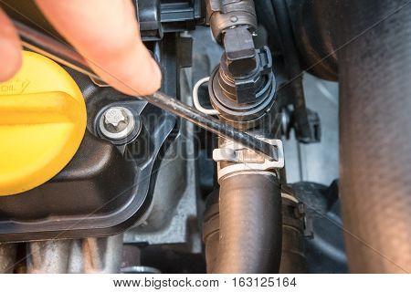 Close up of a hose clamp check with a screwdriver