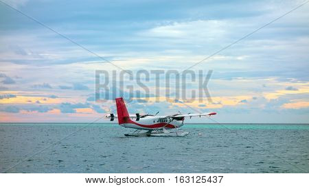 seaplane against the setting sun, the sky rich with dark clouds, rays of light