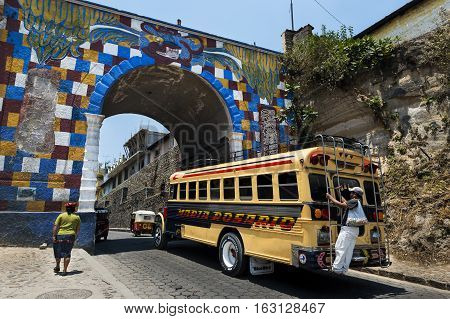 Chichicastenango Guatemala - April 26 2014: Bus with one man holding to a bar in the back entering the town of Chichicastenango in Guatemala