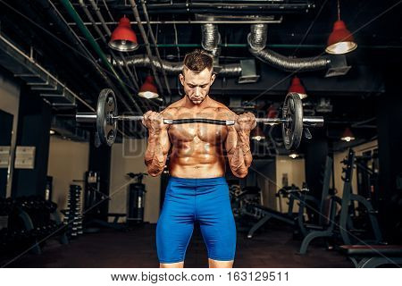 Young handsome caucasian bodybuilder sportsman working out with a barbell in gym, doing biceps training.