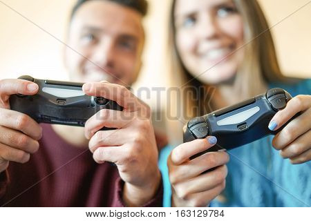 Happy young couple playing video games holding joypads in their apartment - Friends having fun with new console online - People challenging to virtual video games - Warm filter - Focus on man's hand