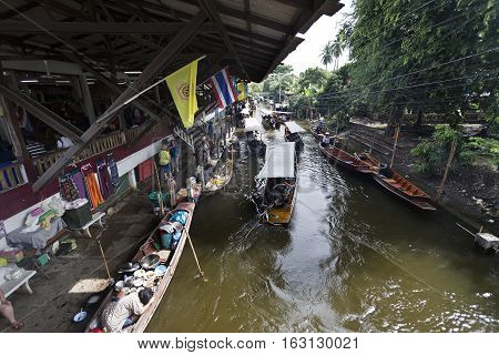 Intense boat traffic in the canals of the floating markets in Bangkok Thailand