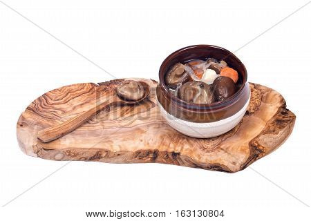 Shiitake marinated mushrooms in ceramic bowl with wooden spoon on olive wood cutting board isolated on white background