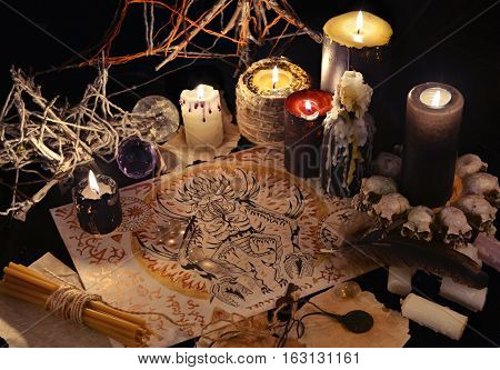 Mystic still life with demon drawing, magic objects and black candles. Halloween concept. Occult objects on table. There is no foreign text in the image, all symbols are imaginary and fantasy ones