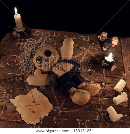 Voodoo doll in pentagram circle on wooden planks. Halloween background, black magic rite or spell with evil candles, occult and esoteric symbols on witch table