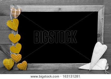Chalkboard With Copy Space For Advertisement. Yellow Hearts. Wooden Background With Vintage, Rustic Or Retro Style. Black And White Image With Colored Hot Spots.