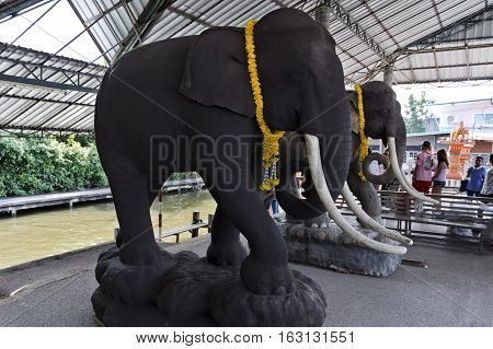 BANGKOK, THAILAND - November 5, 2016: Ceramic statues of full size elephants on a river cruise terminal near the floating markets of Bangkok Thailand
