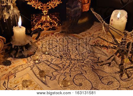 Close up of demon parchment, magic objects and candles.  Halloween concept. Occult objects on table. There is no foreign text in the image, all symbols are imaginary and fantasy