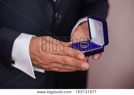 blue box with a ring in a man's hand the bride holding a box with rings
