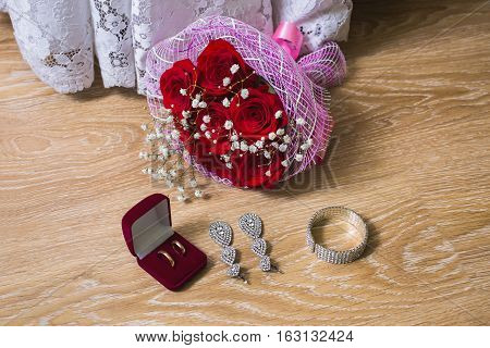 a bouquet of red roses wedding dress wedding rings in red box bride earrings and bracelet on a wooden background preparation for the wedding