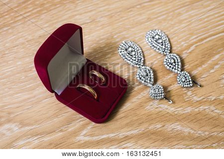 Wedding rings in a red box bride earrings and bracelet on a wooden background preparation for the wedding