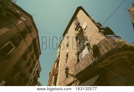 Wide angle view of facades with windows and balconies of old houses in touristic and historic district of Barcelona -El Born sunny summer day Spain.