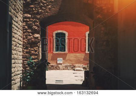 View through stone ancient arc of red wall with curved rectangle window in historical district of Barcelona - El Born on sunny day Spain