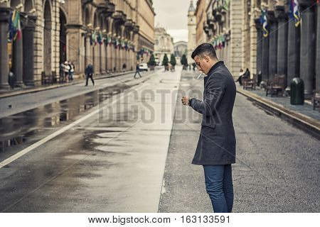 Full length of young man in coat walking under rain along the city street holding cigarette.