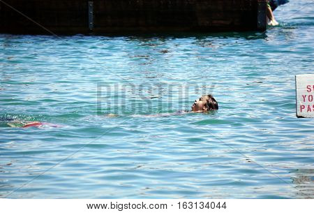 HARBOR SPRINGS, MICHIGAN / UNITED STATES - AUGUST 3, 2016: A girl swims on her back at the Zorn Park Public Beach near downtown Harbor Springs.