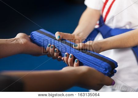 Karate Belt Promotion. Teacher handing belt to youth student. Shallow Depth of Field focus is on the belt.