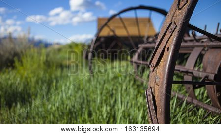 Farming ranch background with barn and rusty farm plow. Green grass blue sky and wooden barn. Shallow depth of field with focus on rusty plow wheel.