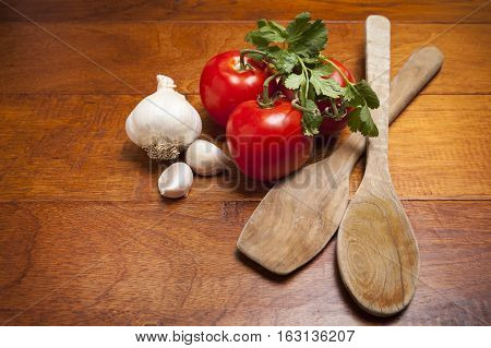 Ripe tomatoes with clove of garlic and wooden spoons on wood cutting board.