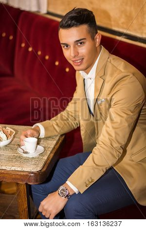 Portrait of smiling handsome man in jacket sitting at table with cup of drink looking at camera