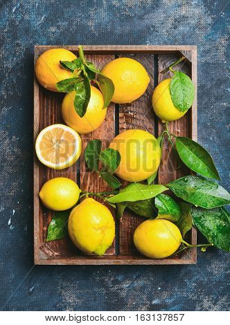 Freshly picked lemons with leaves in rustic wooden tray over dark blue shabby plywood background, top view, vertical composition