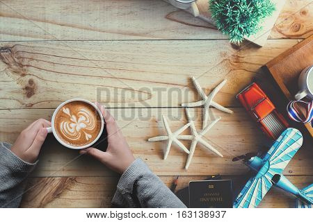 Female holding Cup of coffee Travel Stuff planing on the wood desk. Travel background. Journey planning. Tourist essentials. Space for text or products.