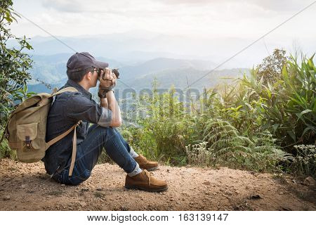 Young professional traveler man with camera shooting outdoor fantastic mountain landscape.