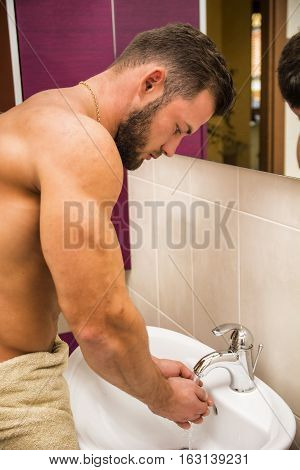 Attractive young man washing his face, splashing water on himself over sink