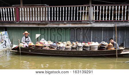 BANGKOK, THAILAND - November 5, 2016: Mother and son selling hats on the floating market of Bangkok Thailand