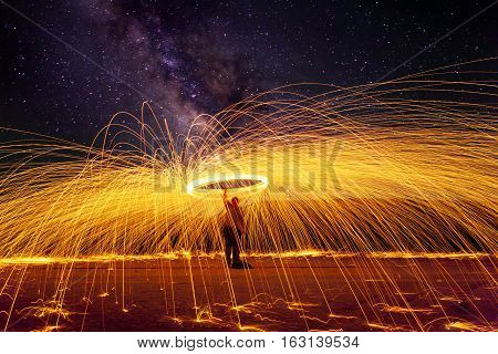 shower of glowing hot sparks with milky way background at night