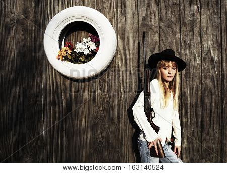 Woman with gun leaning against a wooden wall with white tire with flowers.