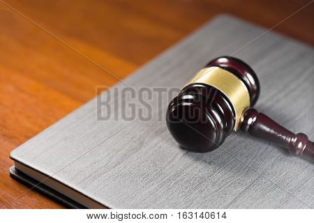 Law gavel on black leather cover of book (concept of justice)