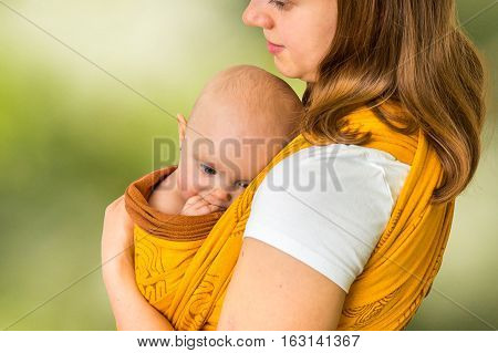 Happy Mother With Her Baby In A Sling - Isolated On Green