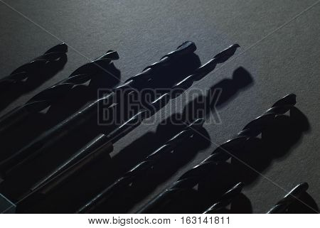 A set of drill bits on wooden background. The symbolic tool repair, black and white, in the dark key