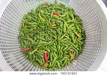 Green chilly and red chilly in the white basket