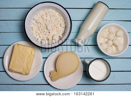 Dairy products on rustic wooden table. Sour cream milk cheese cottage cheese mozzarella yogurt and butter. Top view.
