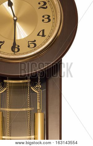Antique wall clock with a pendulum closeup on a white background.